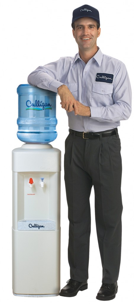 Culligan Man Standing Next to Bottled Water Cooler.